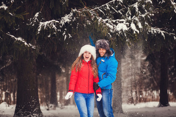 happy couple playing in the winter forest