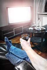 Man with alcohol in hand watching tv