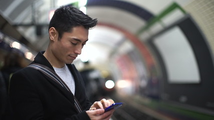 Young man using his phone as a subway train arrives