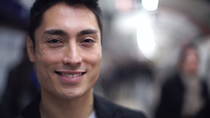 Portrait of young asian man smiling on a subway platform