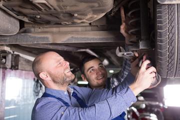 Two man fixing car