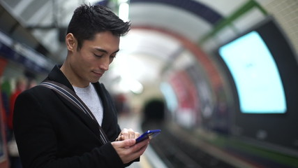 Young man using his phone waiting for his subway train