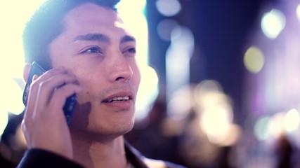 Asian man having a cheerful conversation on his phone at night