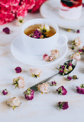 Still life with herbal tea, cake and roses on wooden background