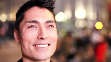 Happy asian man watches a large screen that lights his face