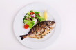 baked whole fish grilled on a plate with vegetables and lemon - 78239217