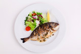 baked whole fish grilled on a plate with vegetables and lemon