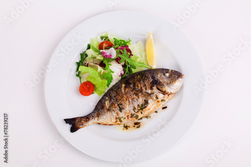 Leinwandbild Motiv baked whole fish grilled on a plate with vegetables and lemon