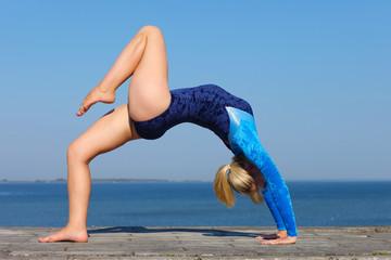 Young gymnast on seashore