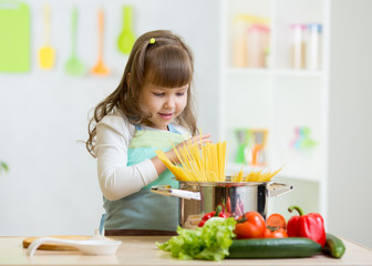 kid girl playing cook and preparing spaghetti