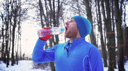 Jogger drinking water after running, steadycam shot, slow motion