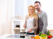 canvas print picture - Young attractive couple cooking in a kitchen