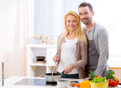 canvas print picture Young attractive couple cooking in a kitchen