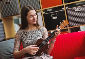 young beauty woman playing on ukelele
