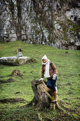 Young female tourist posing with the tree stub