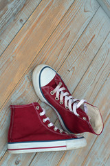red canvas sneakers on a old wooden background