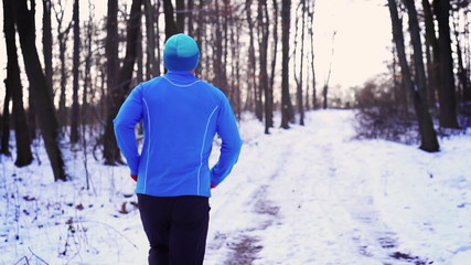 Man running in the forest at winter, steadycam shot, slow motion