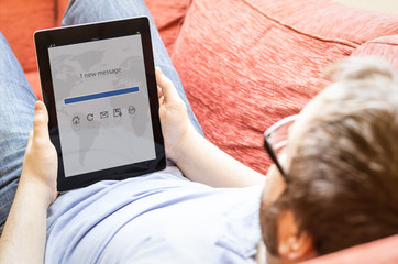 man with tablet at sofa with mail app