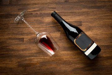Bottle of wine and glass on old wood background.