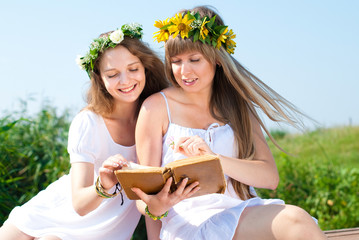 Beautiful Girls with Flowers Wreaths at Summer
