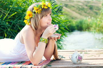 Beautiful Girl with Flowers Wreath drinks tea outdoor
