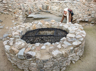 Young female tourist and stone well