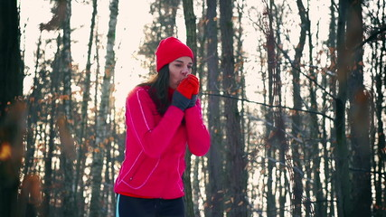 Jogger warming up hands in snowy forest, steady, slow motion
