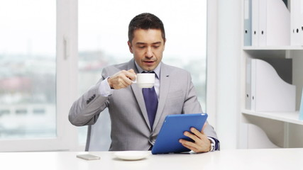 smiling businessman with tablet pc and coffee cup