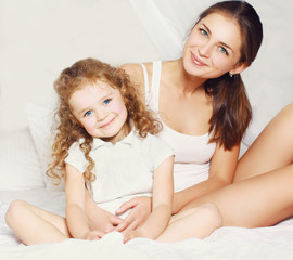 Portrait of beautiful young mother and daughter on the bed