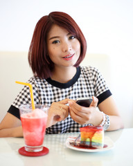 portrait of young asian woman chatting mobile phone with a cake