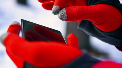 Woman using smartphone in gloves, closeup, steady, slow motion