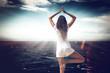 Junge Frau macht Yoga Übungen am Meer