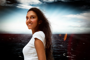 Smiling Indian woman against a dark dramatic sea