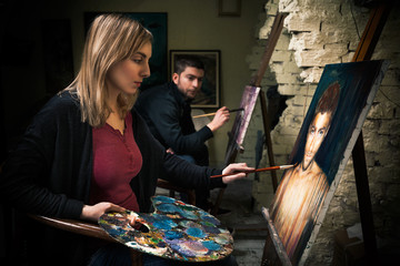 Two young artists working on oil paintings
