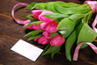 bunch of fresh pink tulips and blank card for text
