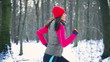 Woman exercising in the snowy forest, steady, slow motion
