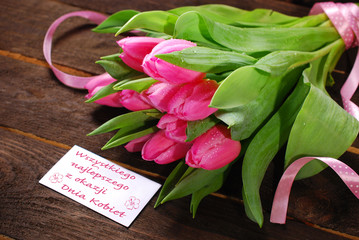 bunch of fresh pink tulips and card with greetings