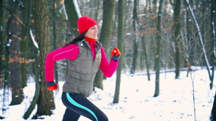 Woman exercising in the snowy forest, steady, slow motion 240fps