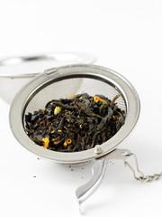 Black leaf tea in a metal sieve on a white background