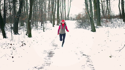 Woman jogging in the snowy forest, steadycam shot, slow motion