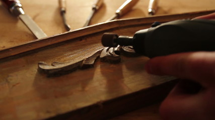 Close up of carpenter sanding wood with engraver tool.