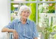 Seniorin sitzt im Wintergarten