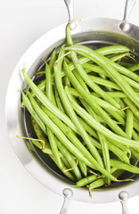 green beans in a saucepan on white