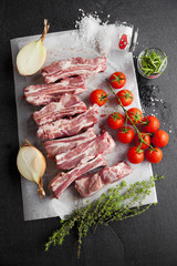 raw pork ribs with cherry tomato and herbs