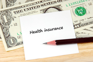 Health insurance word on note pad and money, financial concept