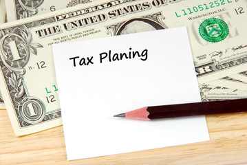 Tax planing word on note pad and money, financial concept