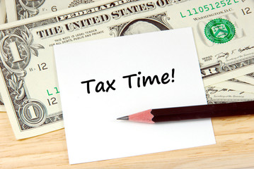 Tax time word on note pad and money, financial concept