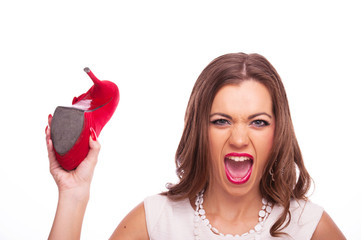Aggressive young woman swinging with red shoe
