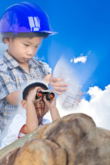 Future engineer, boy lying prone on a boulder and using binocula