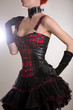 Attractive woman dressed in punk style, plaid leather corset and